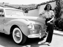 1941: American screen beauty Rita Hayworth (1918 - 1987) poses beside an automobile.